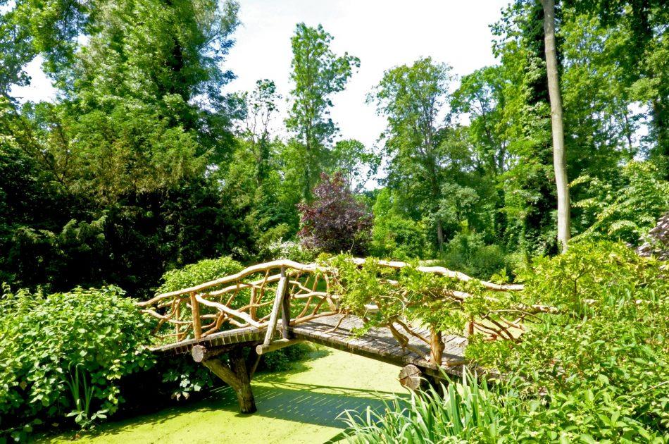 Parkaanleg in Engelse landschapsstijl met houten brug